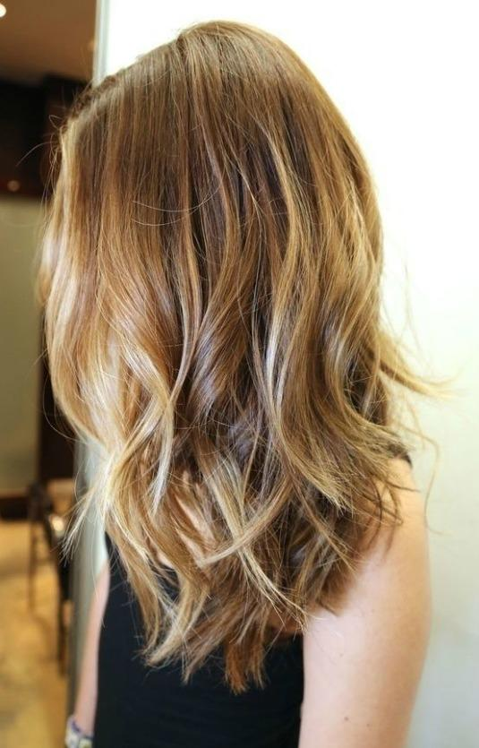 Subtle layers cut into mid-length hair add body and wave to the ends